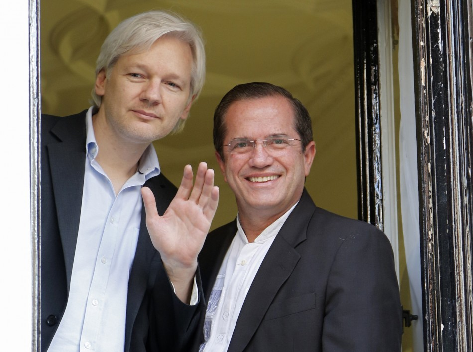 WikiLeaks founder Julian Assange waves from a window with Ecuador's Foreign Affairs Minister Ricardo Patino (R) at Ecuador's embassy