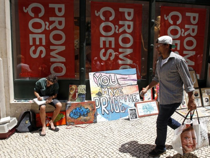 A man walks past a painter selling his work in front of a shop announcing promotions during the general strike in Lisbon June 27, 2013. (Photo: Reuters)