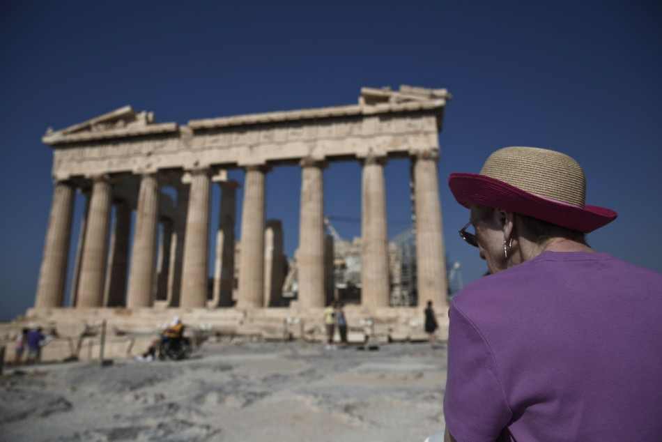 A tourist looks at the temple of the Parthenon atop the hill of the Acropolis in Athens