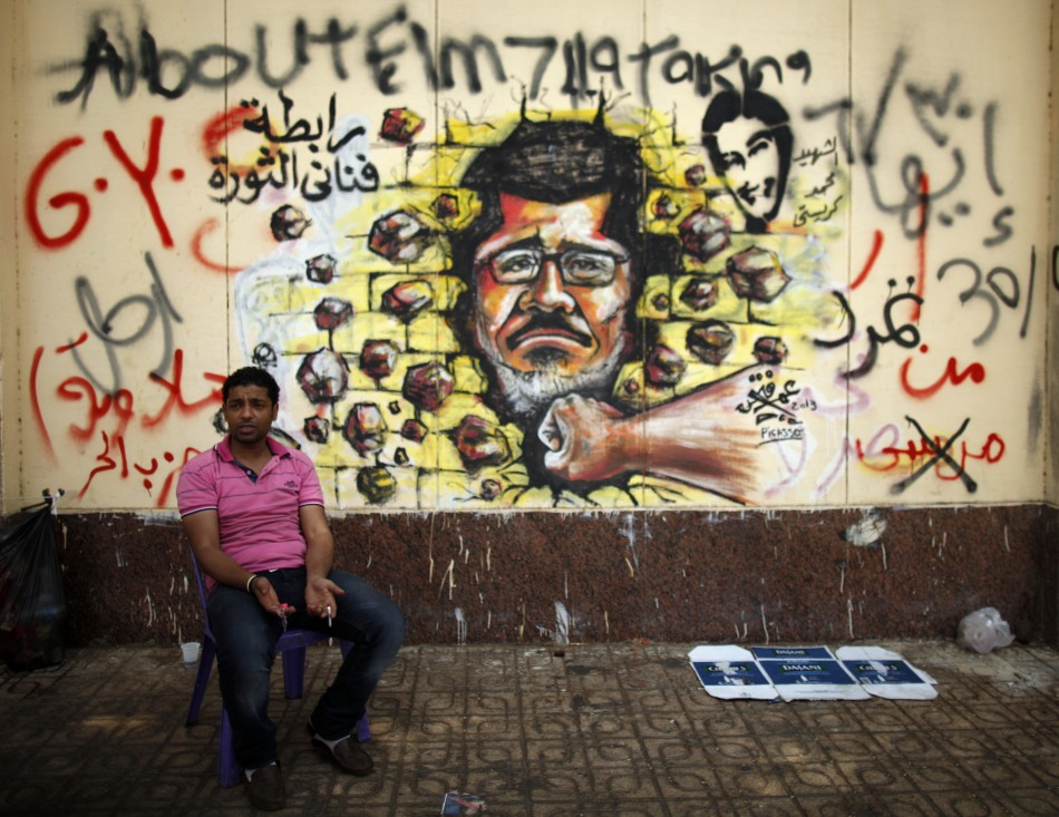 A protester, opposing Egypt's President Mohamed Morsi, sits next to graffiti depicting Morsi on a wall of the Presidential Palace (Reuters0