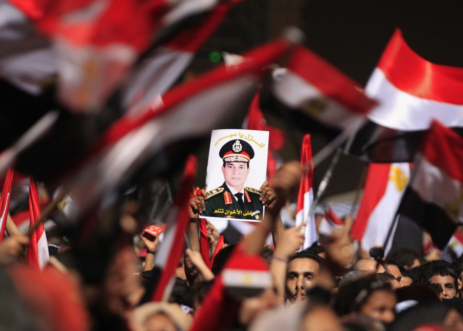 Protesters, who are against Egyptian President Mohamed Mursi, hold a poster featuring the head of Egypt's armed forces General Abdel Fattah al-Sisi