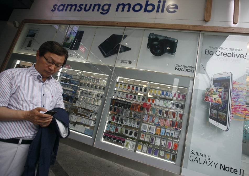 A man uses his mobile phone in front of a Samsung mobile shop in Seoul