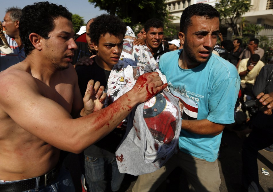 Protesters, who support former Egyptian President Mohamed Mursi, carry the covered body of a victim