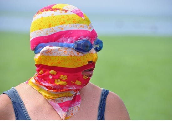 "A woman wearing ""facekinis"" chill out at beach floated with enteromorpha prolifera in Qingdao."