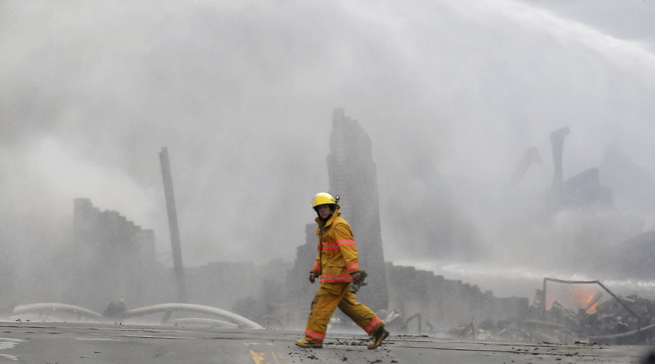 A firefighter walks past the smoking wreck