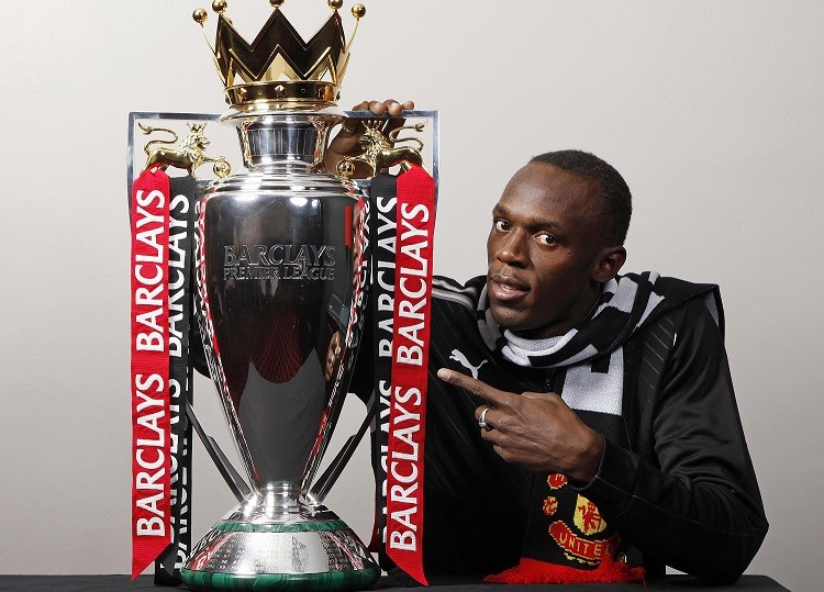 Usain Bolt poses in Man Utd scarf with Premier League trophy