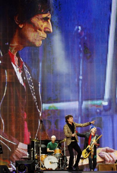 From L to R Ronnie Wood on screen, Charlie Watts, Mick Jagger and Keith Richards