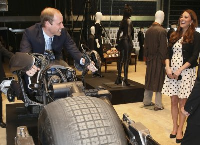 Catherine, Duchess of Cambridge, laughs as her husband Prince William sits on the Batpod, from a Batman film, during their visit to the Warner Bros. Studios at Leavesden in southern England April 26, 2013.