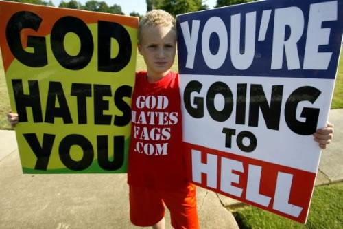 Indoctrinated child brandishes Westboro Baptist Church placards