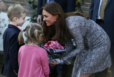 Catherine, Duchess of Cambridge receives flowers from children as she leaves Hope House addiction treatment centre after an official visit in London February 19, 2013.