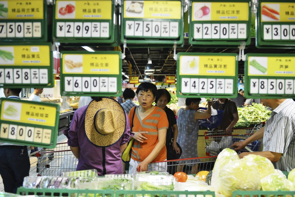 A customer looks at vegetables under price tags at a supermarket in Hangzhou