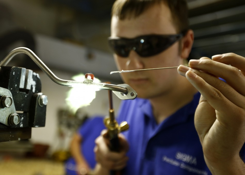 A worker brazes a component at a manufacturing firm in Hinckley, central England