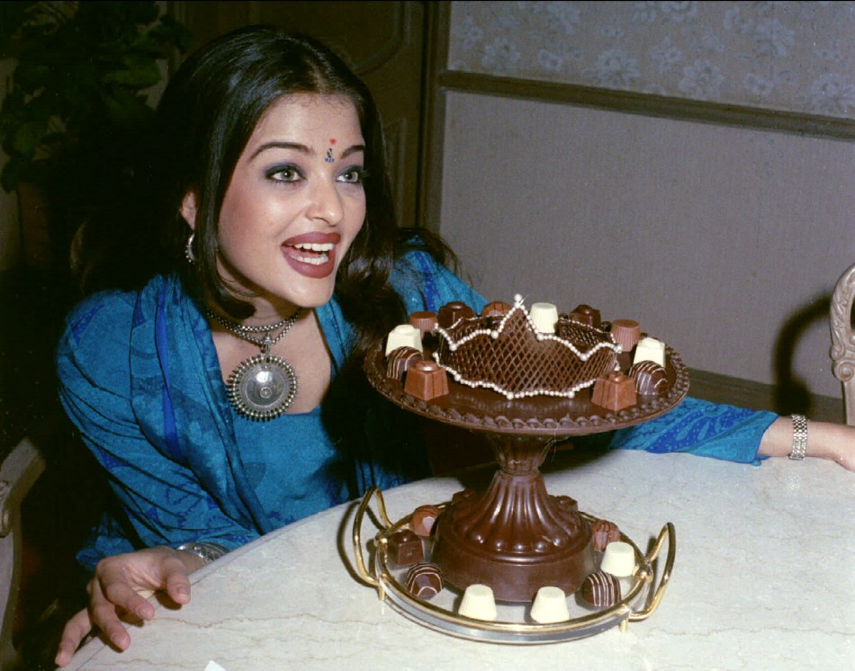 New Indian Miss World Aishwarya Rai looks longingly at a plate of chocolates shaped in a crown after returning to her home city of Bombay December 16