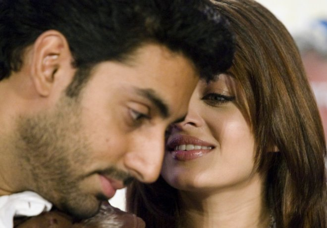 Bollywood actors Abhishek Bachchan and Aishwarya Rai Bachchan (R) speak to the media to promote the