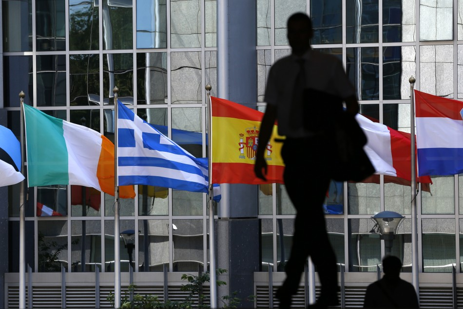A pedestrian walks towards the (L-R) Irish, Greek, Spanish, French and Dutch national flags outside the European Parliament in Brussels (Photo: Reuters)