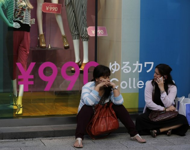 Women sit in front of a clothing store in Tokyo