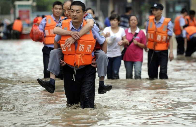 Chengdu policeman carries a flood victim to safety