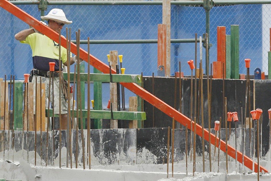 A man moves a plank of wood while working at a construction site for a mall in central Sydney