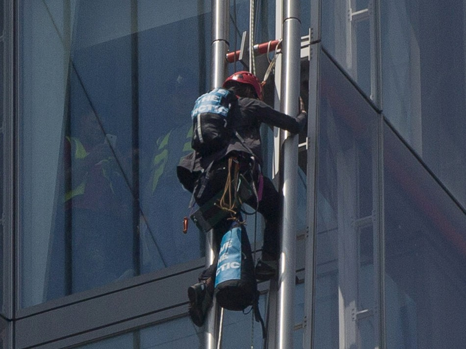 A Greenpeace demonstrator climbs the Shard building (Reuters)