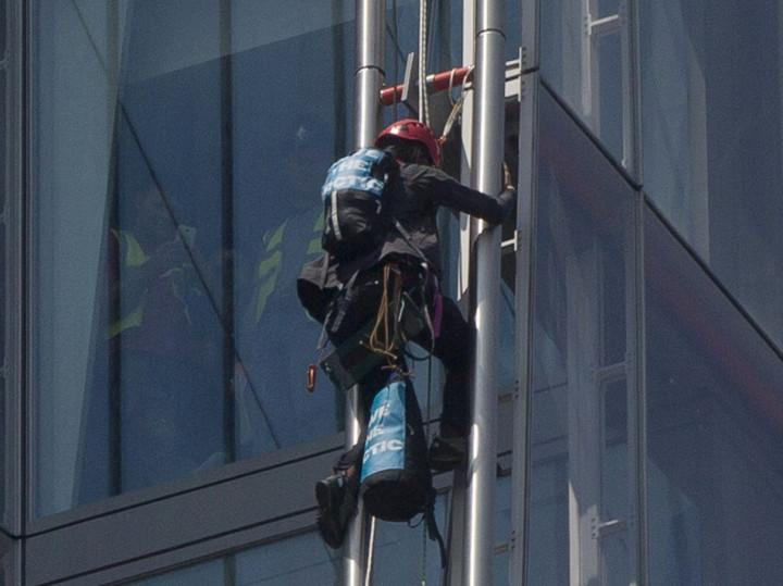 A Greenpeace demonstrator climbs the Shard building (Reuters)