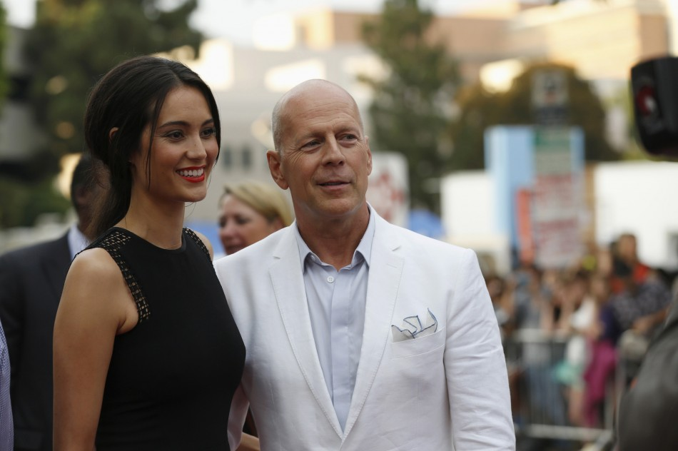 Cast member Bruce Willis and his wife Emma Heming pose at the premiere of the film Red 2 in Los Angeles, California July 11, 2013.