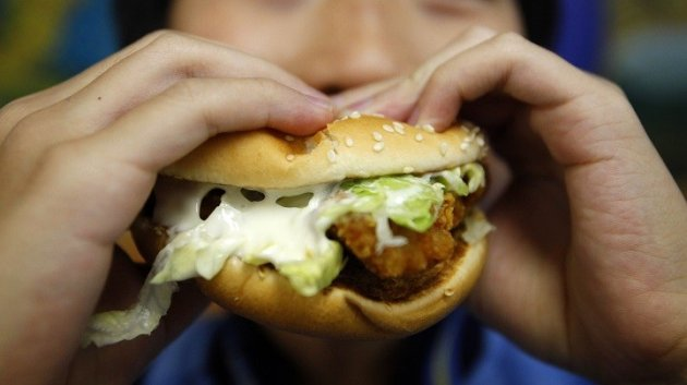 Sticky fingers: Child tucks in to chicken burger
