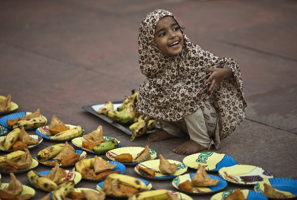 A Muslim girl arranges plates before iftar breaking fast meal on the first day of the holy month of Ramadan in India at the Jama Masjid Grand Mosque in the old quarters of Delhi