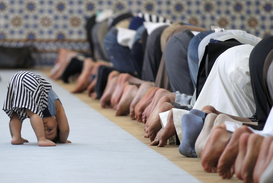 A child is seen near members of the Muslim community attending midday prayers at Strasbourg Grand Mosque in Strasbourg on the first day of Ramadan July 9, 2013. The Grand Mosque of Paris has fixed the first day of Ramadan