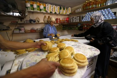 A Palestinian woman buys qatayef, a dessert traditionally eaten during the Muslim holy fasting month of Ramadan, on the first day of Ramadan in the West Bank city of Ramallah