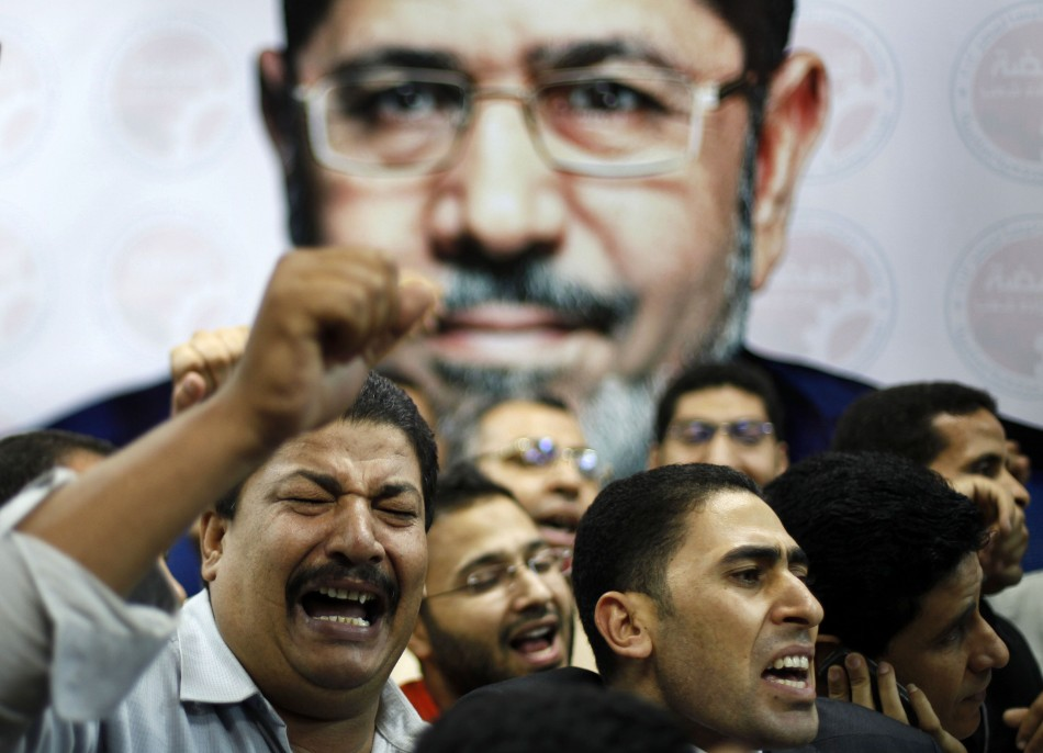 Supporters of the Muslim Brotherhood's presidential candidate Mohamed Morsi celebrate in front of his picture at his headquarters in Cairo (Reuters)