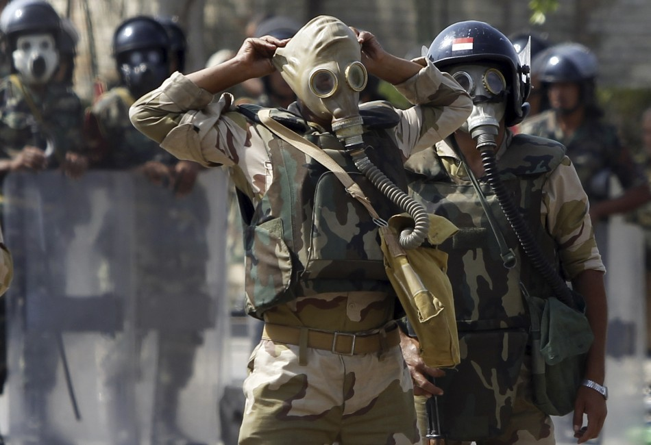 Army soldiers wear gas masks before clashes with members of the Muslim Brotherhood and supporters of Morsi (Reuters)