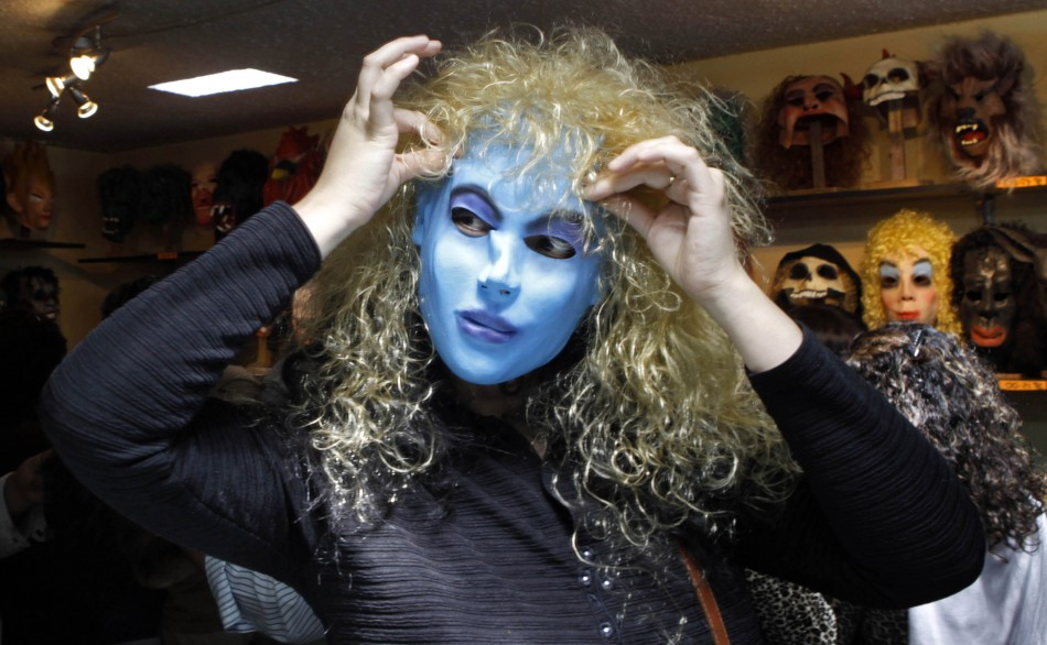 A woman tries on a mask from the film Avatar