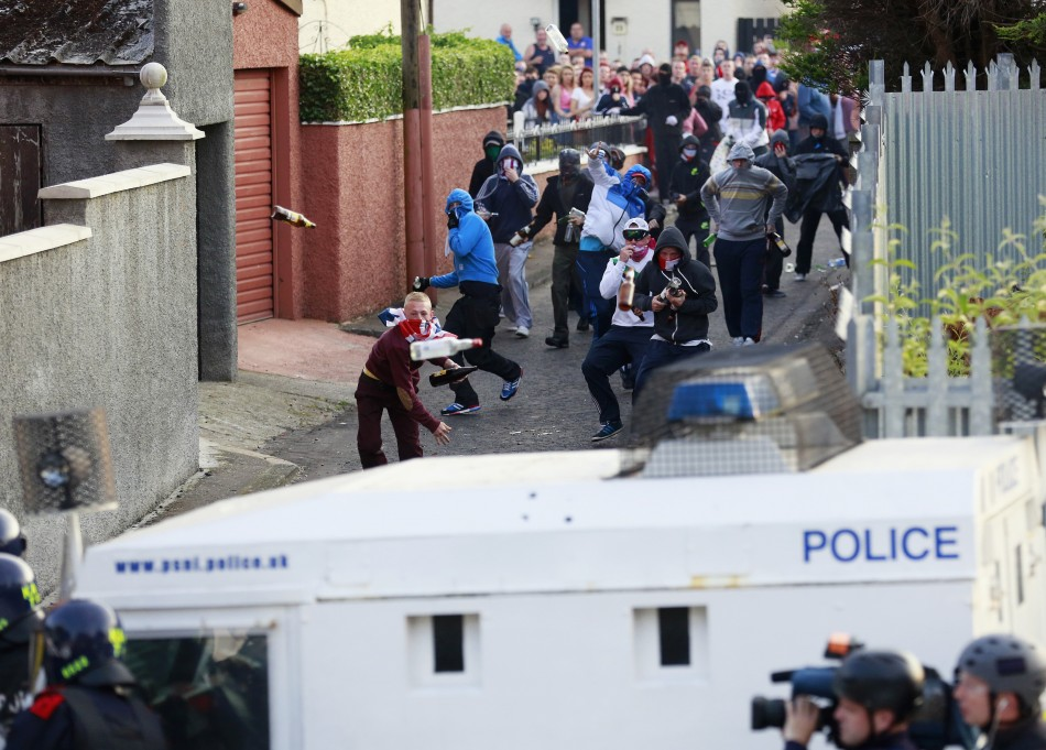 A rioter hurls a bottle at police during rioting in Woodvale, Belfast yesterday.