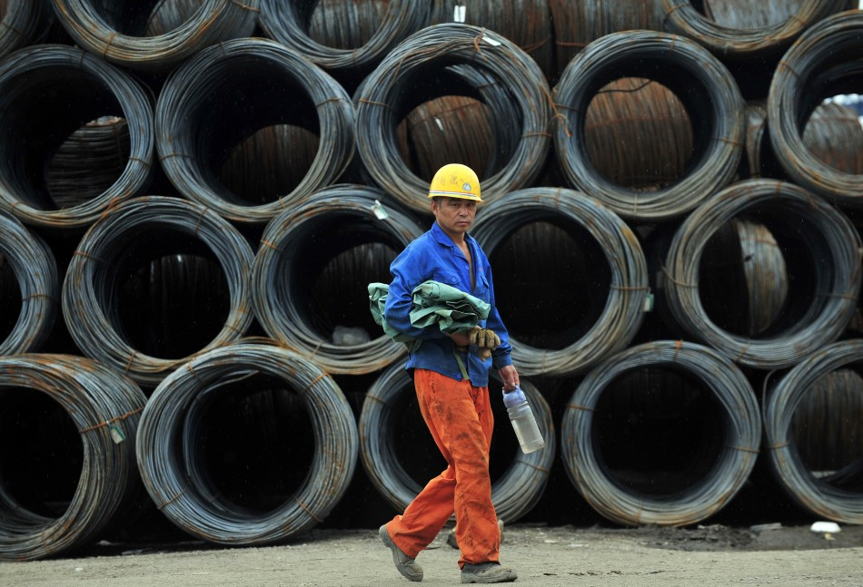 A labourer walks past piles of steel coils at a steel wholesale market in Shenyang.