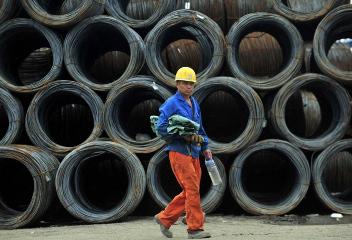A labourer walks past piles of steel coils at a steel wholesale market in Shenyang