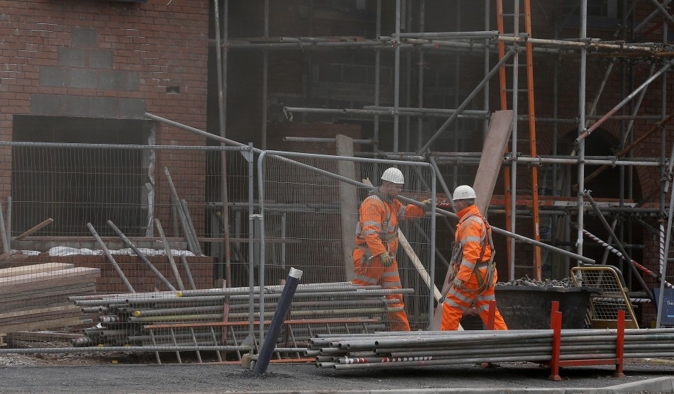 Workers carry scaffolding on a construction site in Chester, northern England
