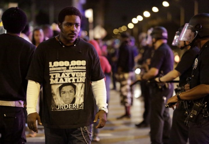 A protester defiantly walks past a line of Los Angeles Police officers as they try to remove protesters from the streets, following the George Zimmerman verdict