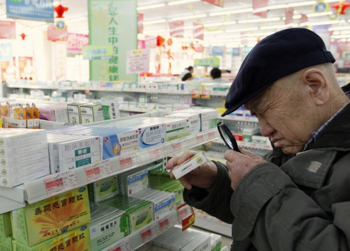 A customer casts a close eye over the product in a Chinese pharmacy