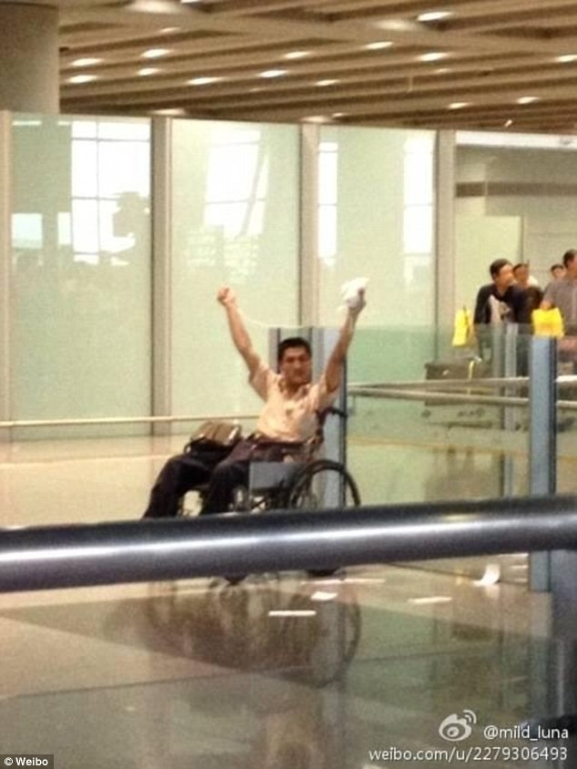 A man is pictured waving a package over his head minutes before an explosion at Beijing Airport.