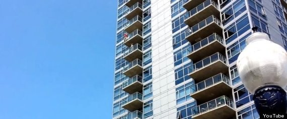 A woman dangles from the 14th floor of The Mark condominium building in San Diego