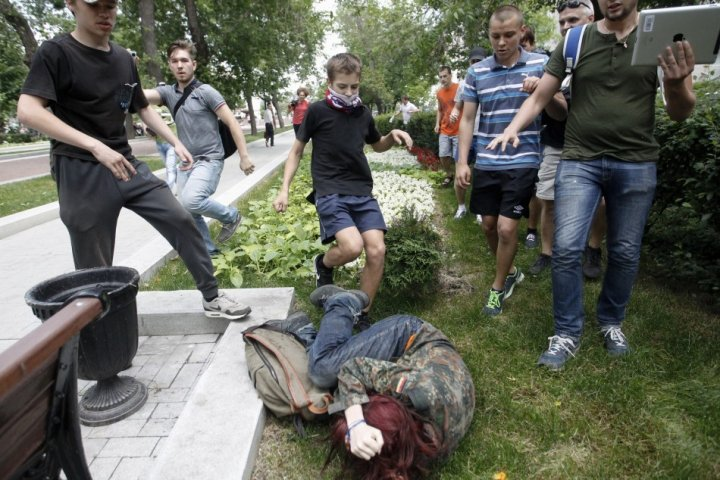 Youths kick a gay rights activist during a protest against the law before it passed (Reuters)