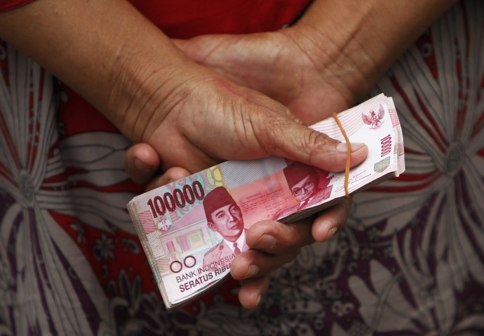 A woman holds Indonesian rupiah
