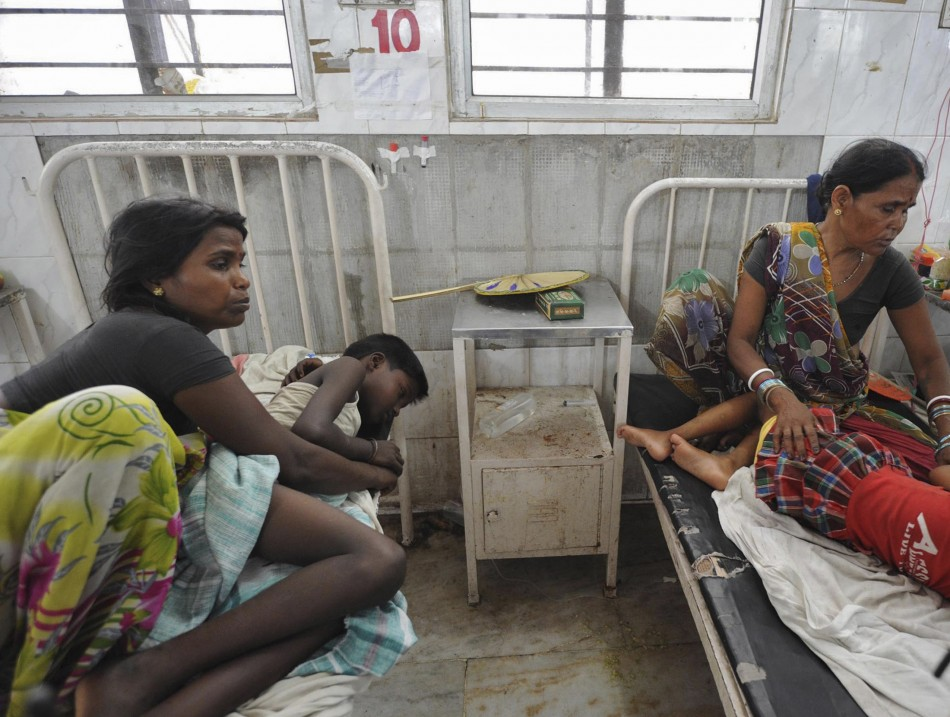 Women sit next to their sick children who consumed the contaminated meal (Reuters)
