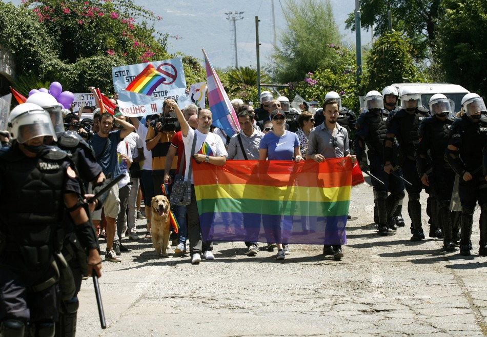 Riot police protect LGBT activist during the parade (Reuters)