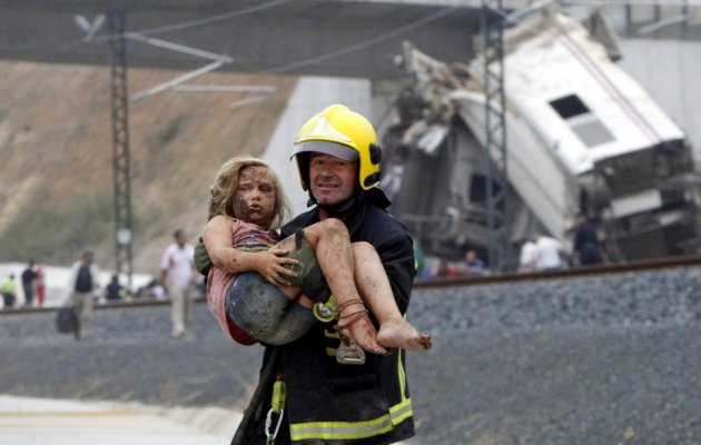 A rescue worker carries a little girl to safety from the train wreck in Santiago de Compostela
