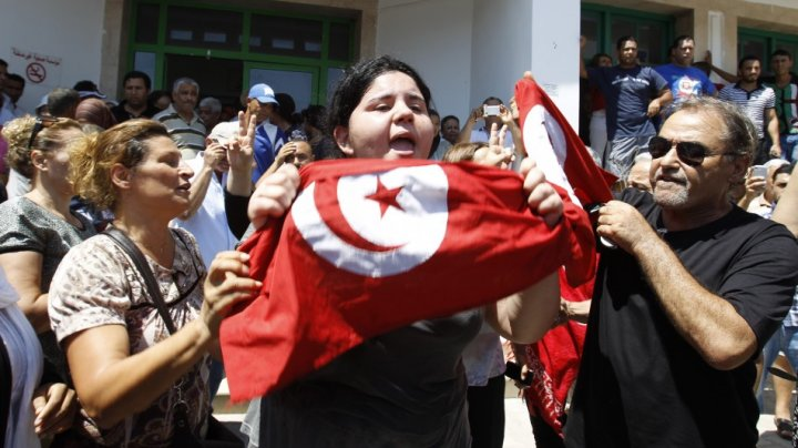 Assassinated Tunisian opposition politician Mohamed Brahmi's daughter Balkis (C) holds a Tunisian flag as she mourns his death in Tunis