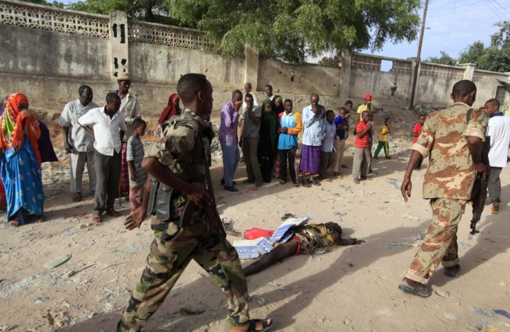 Somali police walk past the body of a suspected al Shabaab militant who was killed in an explosion while attempting to plant a roadside bomb in the capital Mogadishu