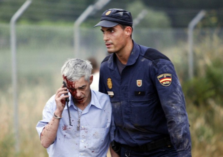 Francisco Jose Garzon Amo is led away by a police officer after the crash