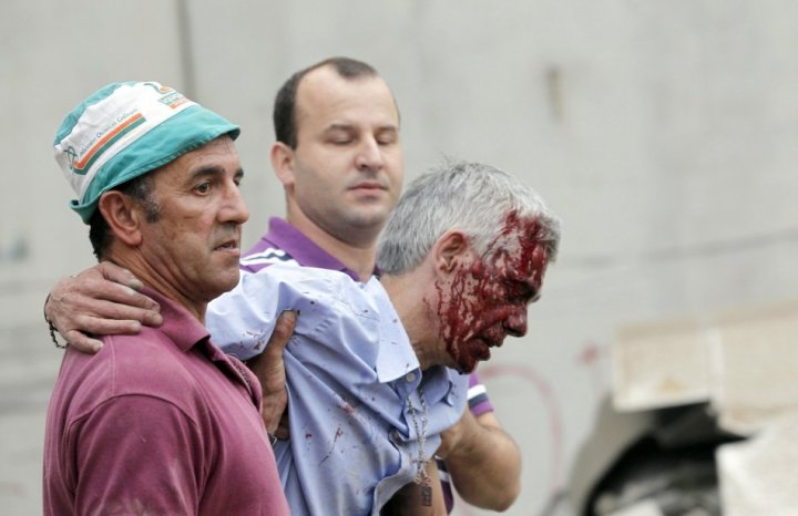 Francisco Jose Garzon Amo (centre )is supported by two men after Wednesday's crash