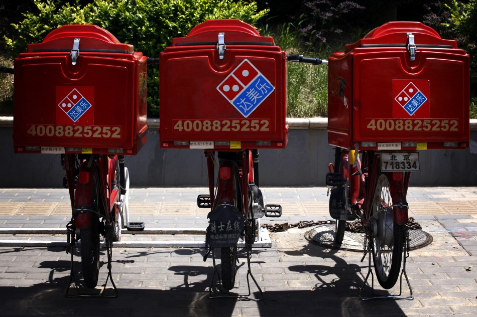 Three electric bicycles used to deliver Domino's Pizzas can be seen parked on the footpath.